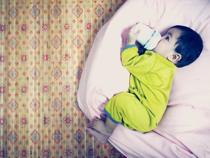 Cute Boy Drinking Milk From Bottle While Lying On Bed