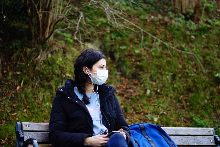Young woman wearing mask sitting on bench