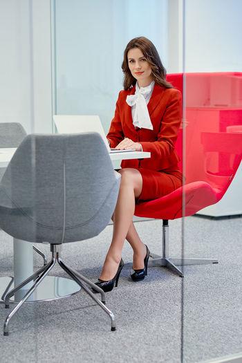 Portrait of businesswoman using laptop in office seen through doorway