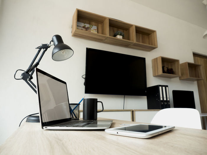 The interior of the modern office has no people. Technology Table Wireless Technology Indoors  Communication No People Computer Connection Still Life Laptop Business Lighting Equipment Cup Modern Mug Wood - Material Electric Lamp Furniture Seat Coffee Cup