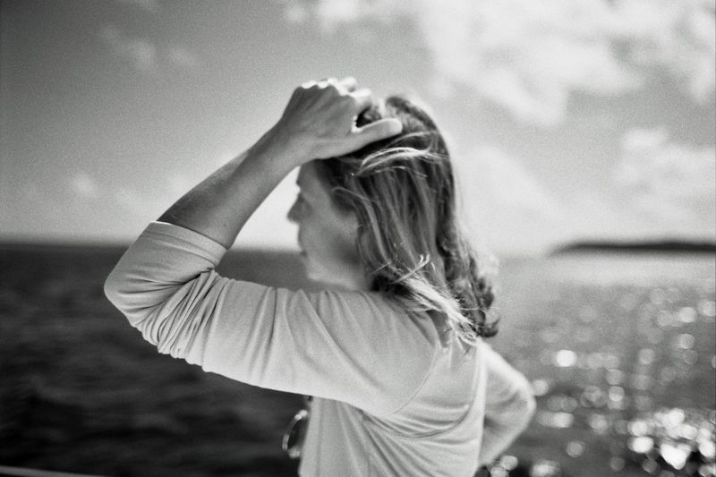 Woman with hand in hair against sea