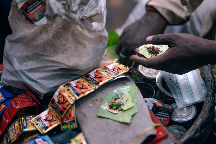Paan Stall Indian Ingredients Market Addiction Artist Chew Chewing Close-up Day Holding Human Body Part Human Hand Leaf Men Occupation One Person Outdoors Paper People Real People Skill  Spice Spices Working