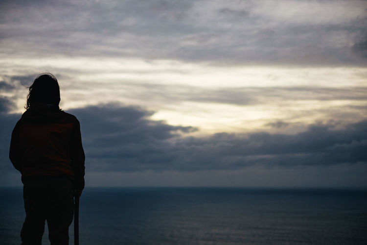 Rear view of man standing in sea against sky
