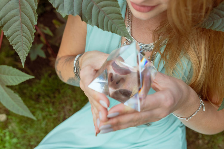 Midsection of woman holding prism while sitting by plant