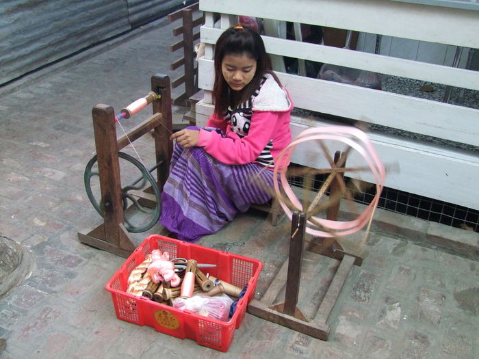 Girl Silk Spinning by Hand Composition Day Female Full Frame Full Length Girl Making A Living Mandalay Manufacturing Myanmar No Incidental People One Person One Woman Only Outdoor Photography Outdoors Silk Thread Sitting Smiling Spinning Wheel Womans Work Working