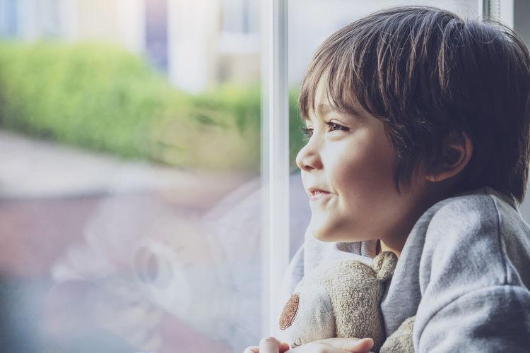 Cute boy looking through window