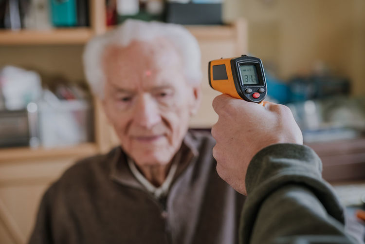 Cropped hand checking temperature of senior man
