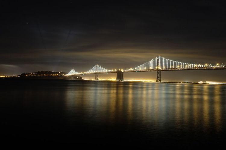 Illuminated bay bridge over river at night
