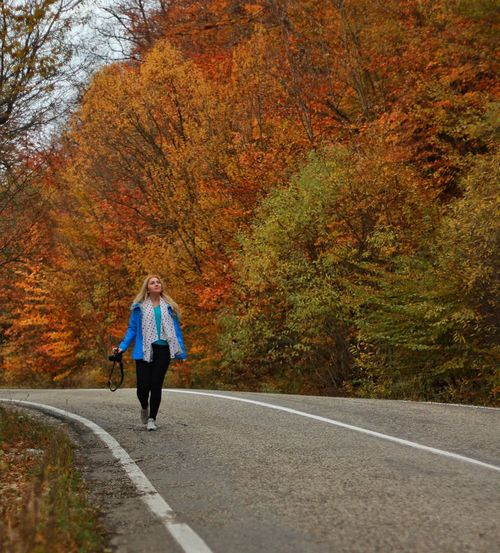 Woman walking with camera on country road against trees during autumn