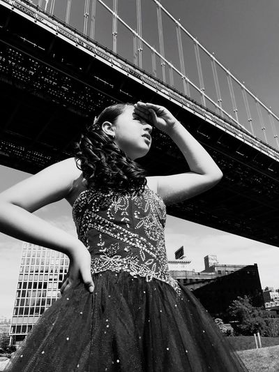 Low angle view of girl shielding eyes while standing against bridge during sunny day