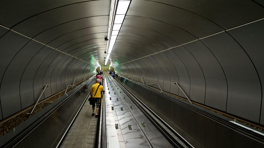 tunnel in the subway Artificial Light Escalators EyeEm Selects Stairs Station Transportation Underground Unrecognizable People Connection Convergence Convergent Diminishing Perspective Mode Of Transport Mode Of Transportation Movement Small Group Of People Subway Tunnel Unrecognizable Person vanishing point