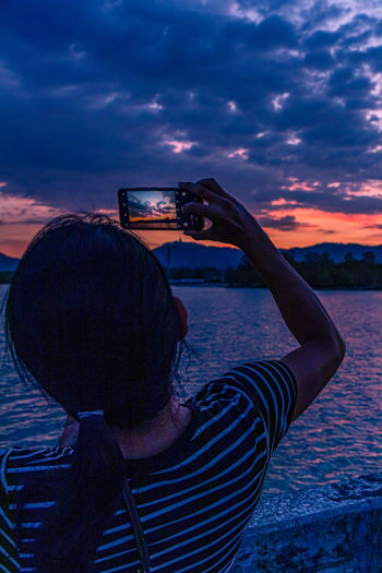Rear view of woman photographing at sunset