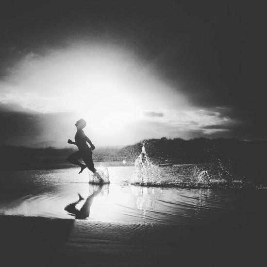 Silhouette person running in water during sunset