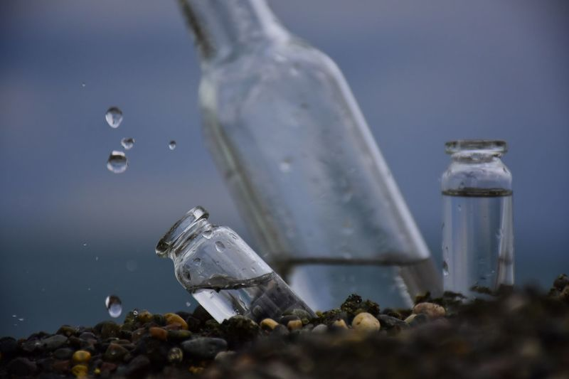 Close-up of bottles on rocks at beach