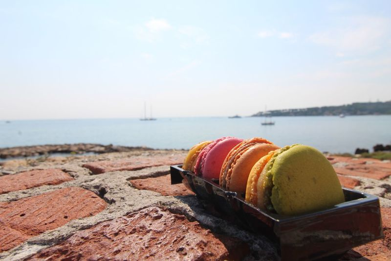 Close-up of macaroons in container at beach against sky