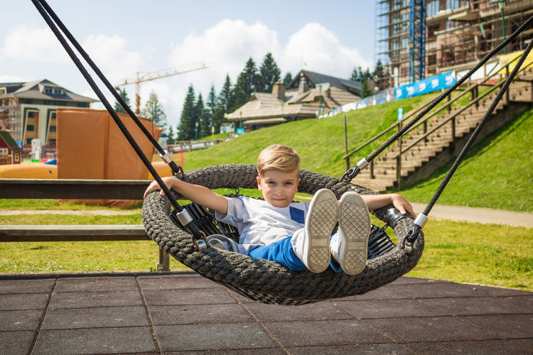 Portrait of boy lying on play equipment at playground