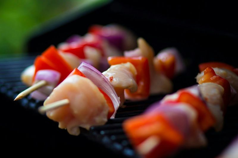 Close-up of prawns and vegetables in skewers on barbecue grill