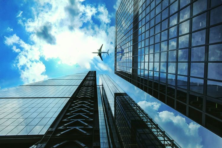 Commercial airplane flying over modern office buildings