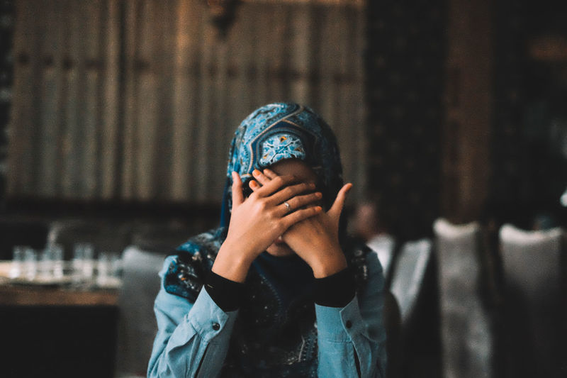 Woman wearing hijab covering face at restaurant