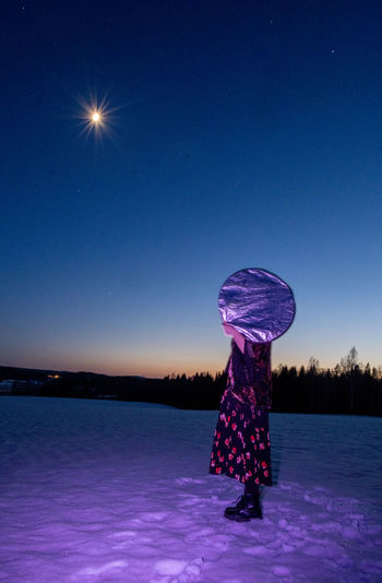 Woman standing on illuminated snow against blue sky at night