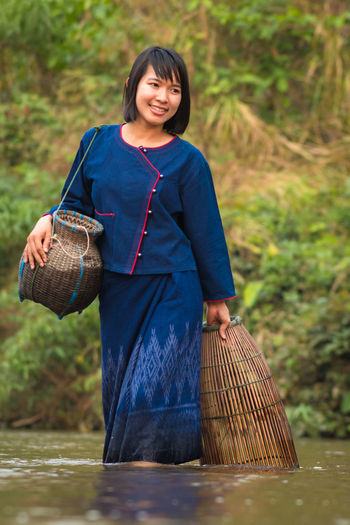 Smiling woman walking in lake with wicker containers