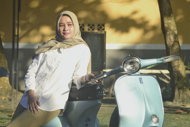 Young woman standing on motor scooter