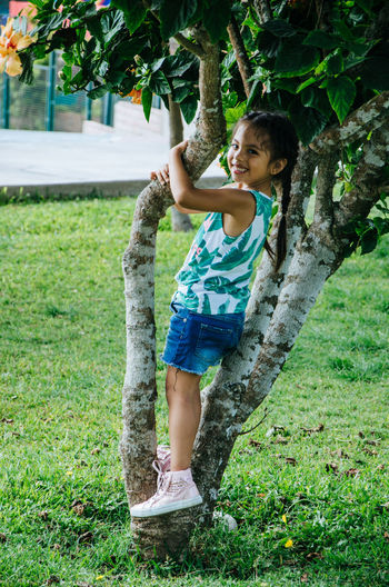 Side view portrait of girl smiling while standing on tree at park