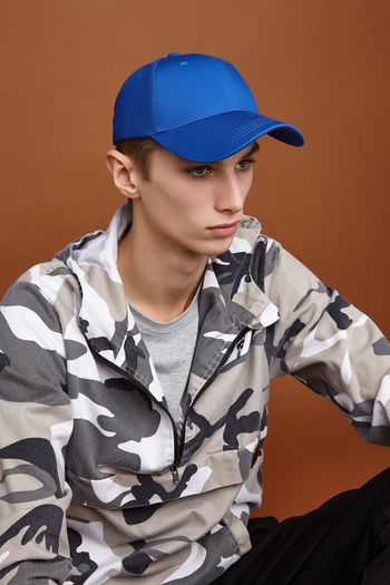Young man looking away against gray background