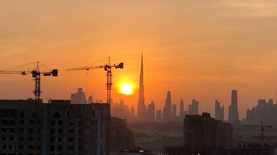 Burj Khalifa Dubai Architecture Sky Built Structure Building Exterior Sunset City Building Orange Color Sun Silhouette Landscape Construction Site Urban Skyline Crane - Construction Machinery