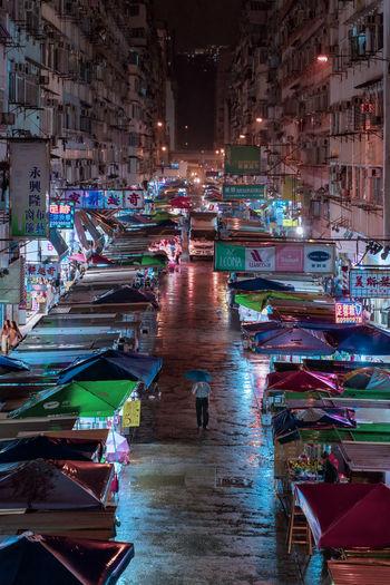High angle view of man at illuminated night market in city