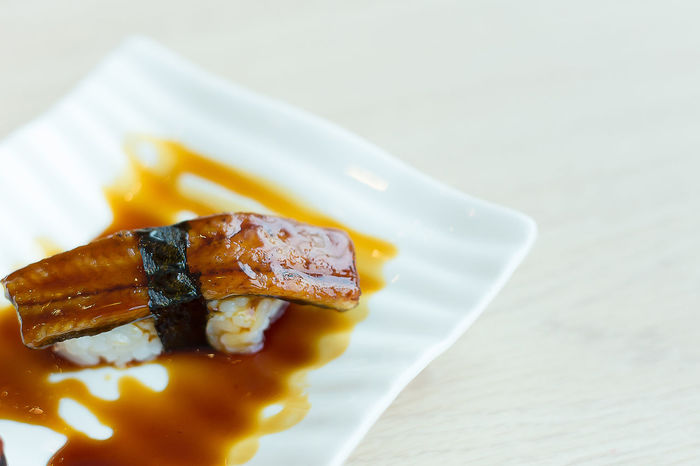 The image close up unagi sushi on white mood in japanese restaurant Close-up Day Food Food And Drink Freshness Healthy Eating Indoors  No People Plate Ready-to-eat Serving Size Table Unagi Don Unagi Sushi