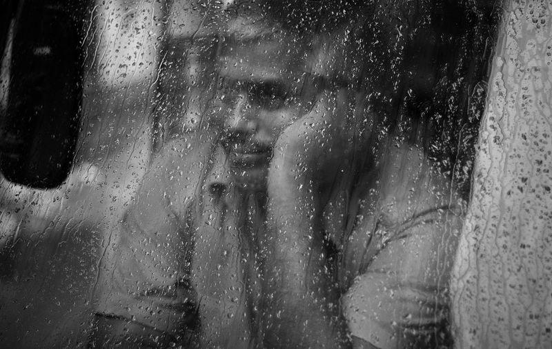 Woman seen through wet window in rainy season