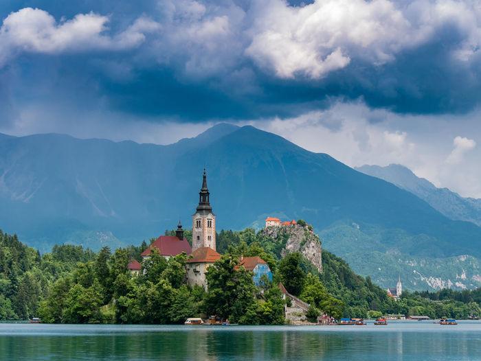 Church by lake against cloudy sky