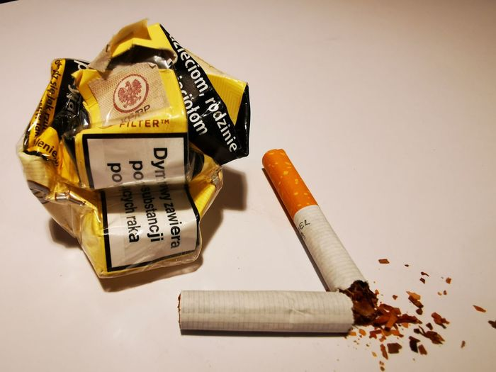 High angle view of cigarette on table against white background