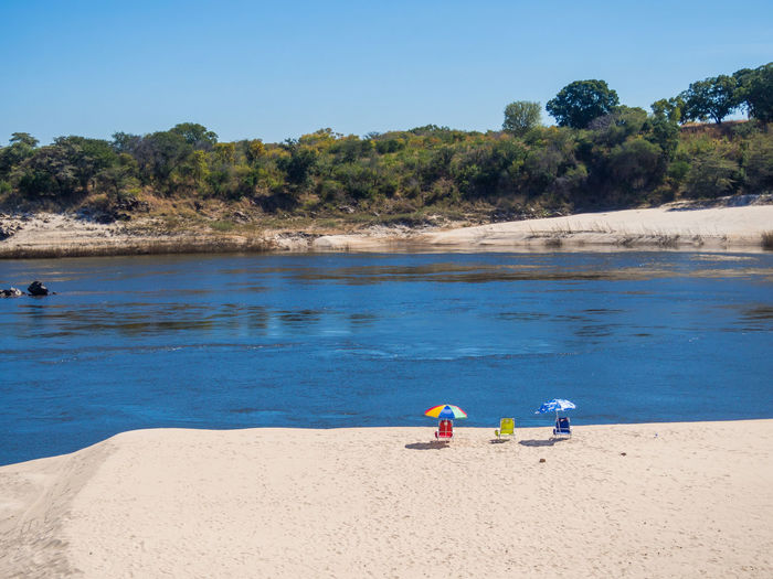Three sun loungers with umbrellas on deserted beach of river zambezi against clear sky, zambia