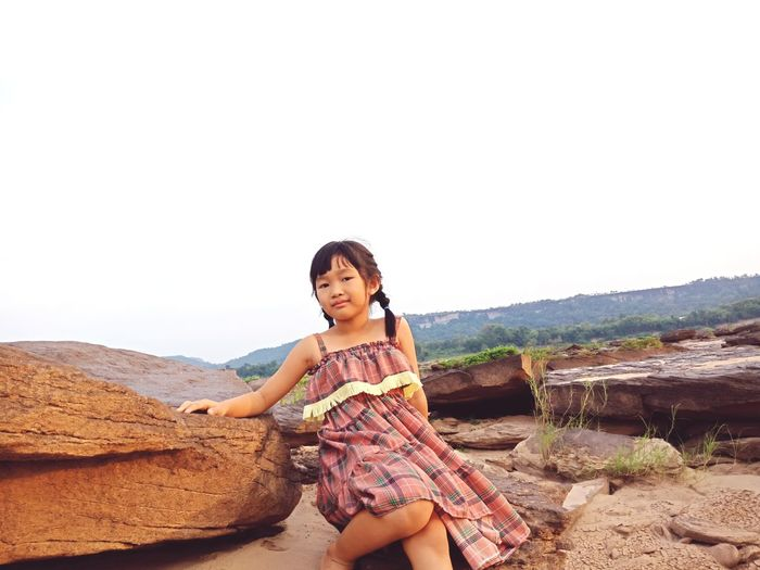 Portrait of girl sitting on rocks against clear sky