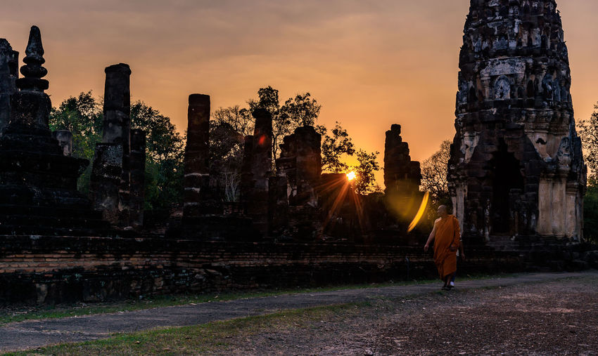 Monk Walking At Historic Temple Against Sky During Sunset