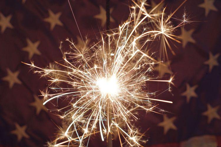 Close-up of sparkler against flag