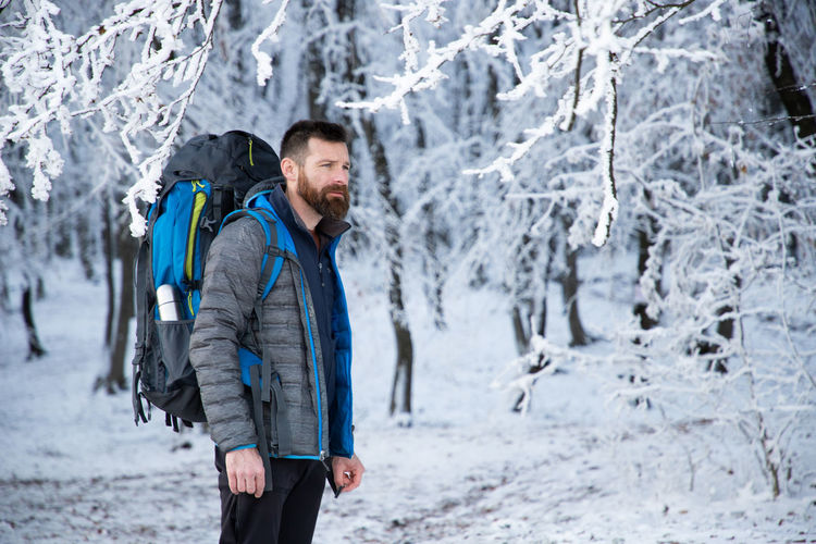 Mature man with backpack standing against snow covered trees during winter