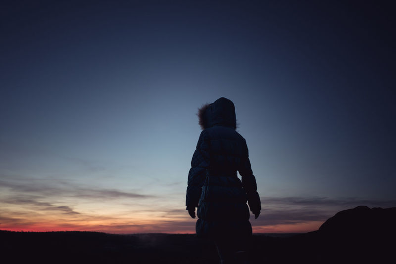 Silhouette of a woman wearing blue winter jacket with hood on looking at distance during sunset Finland Silhouette Copy Space Calm Tranquility Peaceful One Person Silhouette Rear View Only Women One Woman Only Adult Mid Adult Adults Only Sunset People Sky Night Standing Outdoors One Young Woman Only Young Adult EyeEm Ready
