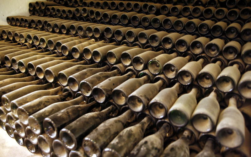 Stack of dust covered wine bottles in warehouse