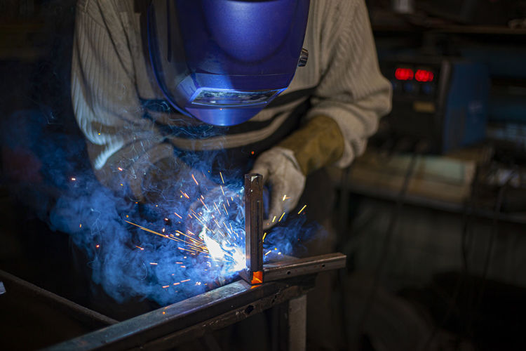 Midsection of welder working in workshop