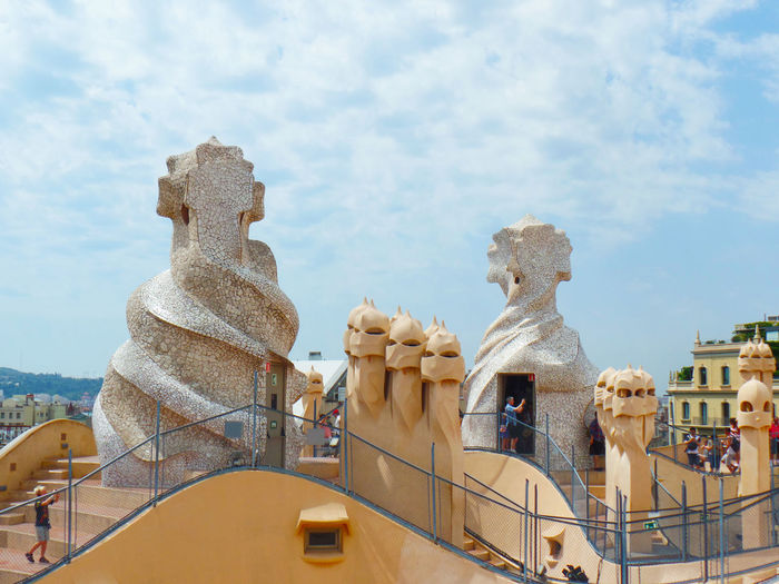 Sculptures in city against cloudy sky