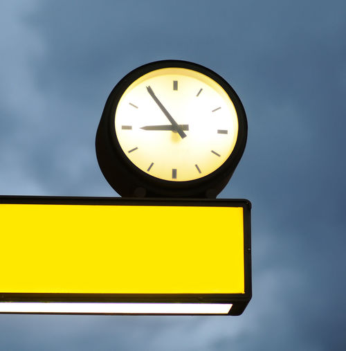 Low angle view of illuminated clock against sky
