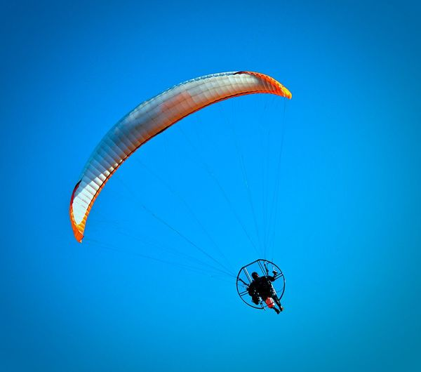 Low Angle View Of Man Motorized Paraglider In Sky