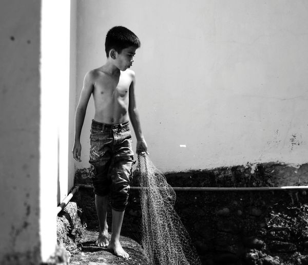 Full length of shirtless boy looking away while holding fishing net against sky