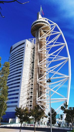 Low angle view of ferris wheel and buildings against blue sky