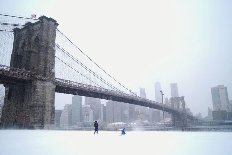 Suspension bridge over snowy landscape against sky