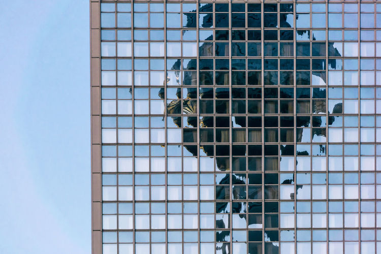 Reflection on modern building against sky