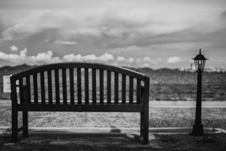 Empty bench on promenade against cloudy sky